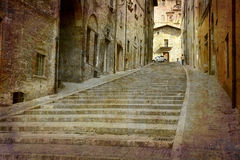 Postcards from Italy (series). Artistic work of my own in retro style - Postcard from Italy. - Steep alley Gubbio, Umbria, Italy Royalty Free Stock Photo