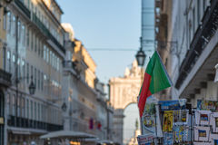 Postcards and National Flag inside Exhibitor in Lisbon Shop, Por. Postcards and National Flag inside Exhibitor and Rua Augusta Arch in background in Lisbon Shop Royalty Free Stock Image
