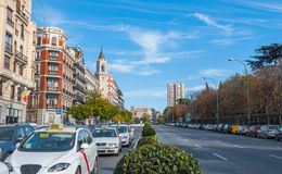 Postcards from Spain.  Taxis in traffic wait for the light on Alica street in Madrid, Spain. Royalty Free Stock Photography