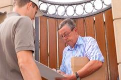 Postdienst - Anlieferung eines Pakets Stockbild