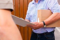 Postdienst - Anlieferung eines Pakets Stockfotos