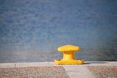 Poste de amarração amarelo no cais com opinião do mar imagem de stock