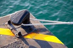 Poste de amarração no porto com a corda dada laços ao redor Fotos de Stock Royalty Free