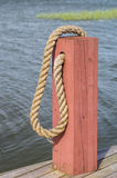 Poste de amarração e corda de madeira vermelhos do barco Imagens de Stock Royalty Free
