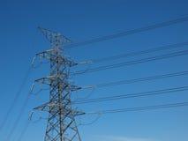Poste de la electricidad del poder más elevado en cielo azul Foto de archivo libre de regalías