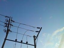 Poste de la electricidad en cielo azul Imagenes de archivo