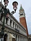 Poste de luz com o Campanile do ` s do vidro Venetian e do St Mark foto de stock