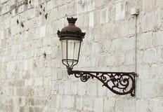 Poste de luz velho em uma parede foto de stock royalty free
