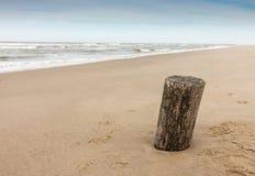 Poste de madera en la playa Imagenes de archivo
