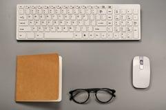 Poste de travail de bureau avec un clavier, une souris, un carnet et des verres Photos libres de droits