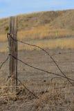 Poste del alambre de púas y de la cerca con el fondo salvaje de la pradera Imagen de archivo libre de regalías