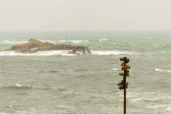 Poste indicador de madera con muchos indicadores con el mar en el fondo foto de archivo