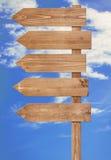 Poste indicador de madera marrón en blanco contra el cielo azul Fotografía de archivo libre de regalías