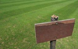 Poste indicador de madera vacío en hierba Fotografía de archivo libre de regalías
