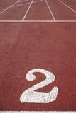 Poste indicador de número dos en una pista corriente atlética Foto de archivo libre de regalías