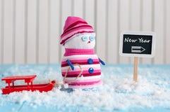 Poste indicador del Año Nuevo y muñeco de nieve con el trineo rojo Fotografía de archivo libre de regalías