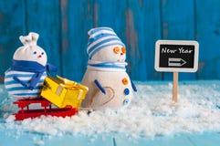 Poste indicador del Año Nuevo y muñeco de nieve dos con rojo Foto de archivo libre de regalías