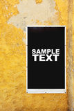 Poster. On yellow shabby wall. Put your own text or image here Royalty Free Stock Photography