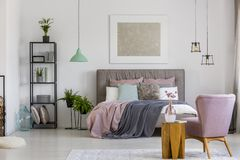 Poster above bed. Modern poster hanging on a white wall above bed in simple room interior with fresh plants Stock Photo
