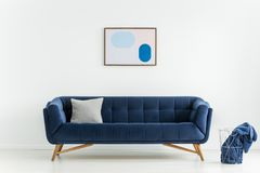 Poster above blue sofa with cushion in white living room interior with blanket in basket. Real photo. Concept stock images