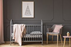 Poster above kid`s bed with blanket next to grey armchair with p Royalty Free Stock Photo