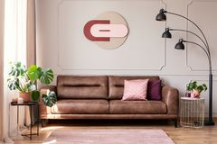 Poster above leather couch with pillows in white flat interior with plants and lamp. Real photo stock image