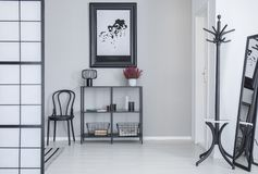 Poster above shelves with flowers and lamp in white simple hall interior with rack and black chair. Real photo royalty free stock photo