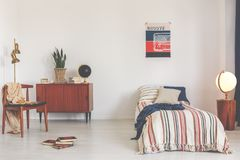 Poster above striped bed in white vintage bedroom interior with chair next to wooden cabinet. Real photo. Concept stock photo