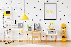 Skateboard in cozy kindergarten interior. Poster above white cabinet with yellow clock between skateboard and wooden desk in cozy kindergarten interior stock photo