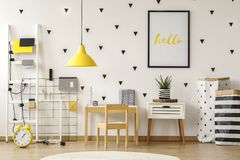 Poster in a black frame on a white wall with stickers in a scandinavian style child bedroom interior with wooden furniture and ye