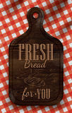 Poster with bread cutting brown wood board letteri. Ng Fresh bread for you on a red checkered tablecloth Royalty Free Stock Image