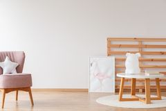 Poster in bright kid`s room. Lamp on wooden stool and poster in bright kid`s room with pink chair and pillow against white wall royalty free stock images