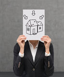 Poster with drawing house. Businesswoman holding poster with drawing house Royalty Free Stock Photo