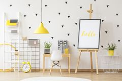 Poster on easel next to wooden desk and white chair in child`s r. Oom interior with yellow lamp. Real photo stock image