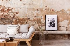 Poster and flowers next to grey wooden couch with pillows in flat interior with brick wall stock photos