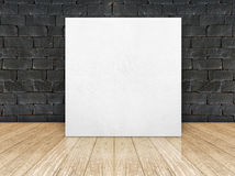 Poster frame at black brick wall and wooden floor Stock Photos