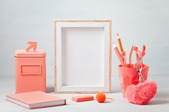 Poster frame with decor elements in living coral color. Poster frame mockup, front view, with decor elements in living coral color, flowers and blank copy space royalty free stock photo