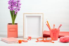 Poster frame with decor elements in living coral color. Poster frame mockup, front view, with decor elements in living coral color, flowers and blank copy space stock photos