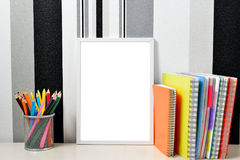 Poster frame mock up template with colored notebooks and can with pencils on wooden table. Minimalistic background stock image