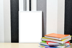 Poster frame mock up template with colored notebooks on wooden table Stock Image