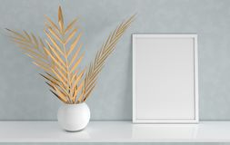 Poster frame mockup with gold palm leaves in the vase on grey background. Front view photo frame on white book shelf or desk. Digitally generated, 3d render stock image