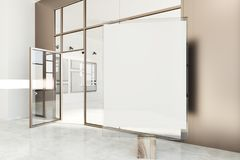 Blank vertical poster in a beige poster gallery. Poster gallery with beige and white walls, a concrete floor and glass doors. A vertical mock up poster in the Royalty Free Stock Images