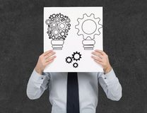 Poster with gears in form lamp. Businessman holding poster with gears in form lamp Stock Image