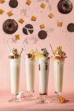Poster with milkshakes. Four glasses of cocktails with straws and sweets - biscuits, chocolate and waffles royalty free stock photos