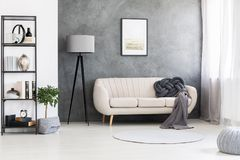 Poster mock-up on a gray, concrete wall and a leather beige sett. Ee in an industrial living room interior with black, wooden furniture royalty free stock photos