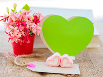 Poster mock up template with flower bouquet,. Marshmallow in the shape of heart and books over green background Royalty Free Stock Photography