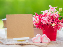 Poster mock up template with flower bouquet,. Marshmallow in the shape of heart and books over green background Royalty Free Stock Photo