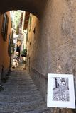 Poster outside an artist`s shop in Varenna, Lake Como. View of one of the many narrow and uphill lane in Varenna, Lake Como Stock Image