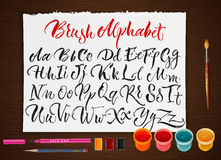 Poster With Paper Sheet With Alphabet. Colorful poster with paints brushes pencils and sheet of paper with hand drawn scrawling alphabet letters flat vector Stock Photo