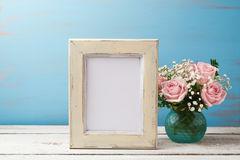 Poster or photo frame mock up template with rose flower bouquet. On wooden table stock photo